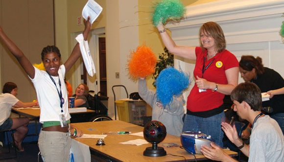 A delegate from the 2009 Kansas YLF celebrates visiting the accommodations table during the Real Life Affair, while volunteers celebrate with her.